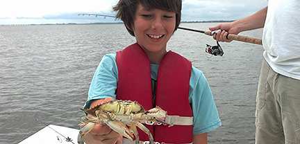 Boy with crab caught aboard Rock On Charters.