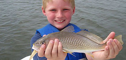 Smiling boy with fish caught aboard Rock On Charters.